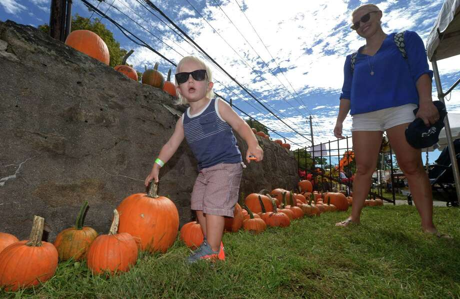 Above, Rhyse Scala, 2, and his mother, Alyssa Scala, of Stamford, pick out pumpkins during the Third Annual St. Philip Family Fall Festival at the church in Norwalk on Saturday. The event featured music, food, face-painting, games for children, arts, crafts, and homemade items. Photo: Erik Trautmann / Hearst Connecticut Media / Norwalk Hour