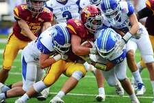St. Joseph's Cole daSilva (42) is tackled by Darien's Will Kirby, left, and John Henry Slonieski, right, during their FCIAC showdown Saturday in Trumbull.