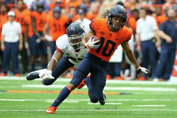 Syracuse's Sean Riley runs with the ball after a catch in front of UConn's Omar Fortt on Saturday.