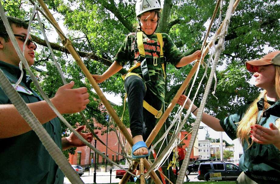 Aaliya Carmen 10, of Derby, crosses a monkey bridge set up by Crew 33 during Ed Strang Day for kids on the Derby Green in downtown Derby, Conn., on Saturday Sept. 22, 2018. Helping Carmen across is Crew 33's Julian Gilloren, and Skylynn Hemstreet. From reptiles and rope bridges to cooking over a campfire, the 24th annual Ed Strang Day will bring the Derby Green to life with challenging adventures for boys and girls of all ages, according to Troop 3 Scoutmaster Randy Ritter. The event pays homage to Scouting Pioneer and Derby Hall of Famer, Ed Strang. Photo: Christian Abraham / Hearst Connecticut Media / Connecticut Post