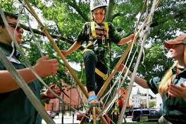 Aaliya Carmen 10, of Derby, crosses a monkey bridge set up by Crew 33 during Ed Strang Day for kids on the Derby Green in downtown Derby, Conn., on Saturday Sept. 22, 2018. Helping Carmen across is Crew 33's Julian Gilloren, and Skylynn Hemstreet. From reptiles and rope bridges to cooking over a campfire, the 24th annual Ed Strang Day will bring the Derby Green to life with challenging adventures for boys and girls of all ages, according to Troop 3 Scoutmaster Randy Ritter. The event pays homage to Scouting Pioneer and Derby Hall of Famer, Ed Strang.