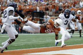 Texas wide receiver Collin Johnson (9) makes a diving catch for a touchdown between TCU defenders Jeff Gladney (12) and TCU safety Markell Simmons (3) during the second half of an NCAA college football game, Saturday, Sept. 22, 2018, in Austin, Texas. (AP Photo/Eric Gay)