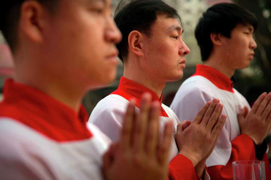 "FILE - In this Saturday, March 31, 2018, file photo, Chinese acolytes pray during a Holy Saturday Mass on the evening before Easter at the Cathedral of the Immaculate Conception, a government-sanctioned Catholic church in Beijing. On Saturday, Sept. 22, 2018, the Vatican announced it had signed a ""provisional agreement"" with China on the appointment of bishops, a breakthrough on an issue that for decades fueled tensions between the Holy See and Beijing and thwarted efforts toward diplomatic relations. (AP Photo/Mark Schiefelbein, File) Photo: Mark Schiefelbein / Copyright 2018 The Associated Press. All rights reserved."
