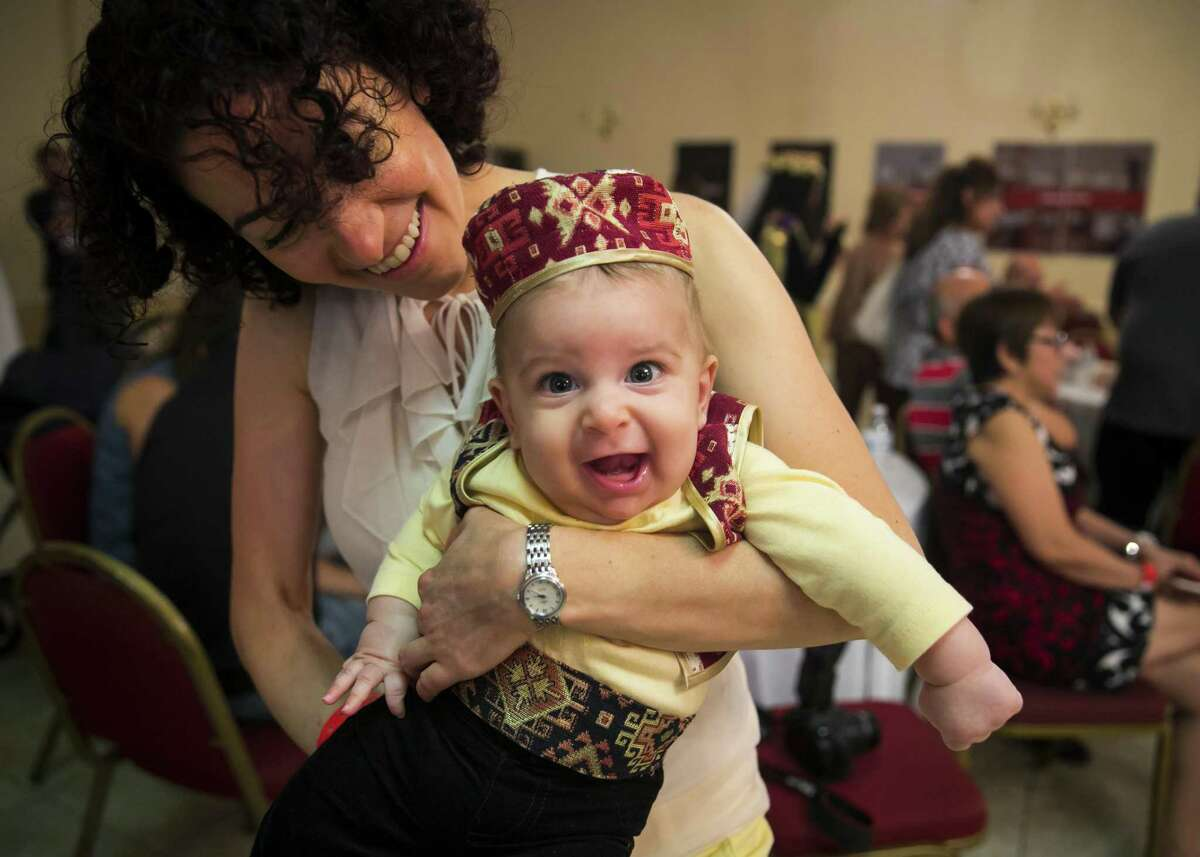 Four-month-old Nicholas Simonian smiles in traditional Armenian clothing in his mother Linda's arms during the 2018 Houston Armenian Festival on Saturday, Sept. 22, 2018, at the Armenian Church of St. Kevork in Houston.