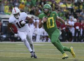 Oregon quarterback Justin Herbert, right, runs down field ahead of Stanford's Jordan Fox during the first quarter of an NCAA college football game Saturday, Sept. 22, 2018, in Eugene, Ore. (AP Photo/Chris Pietsch)