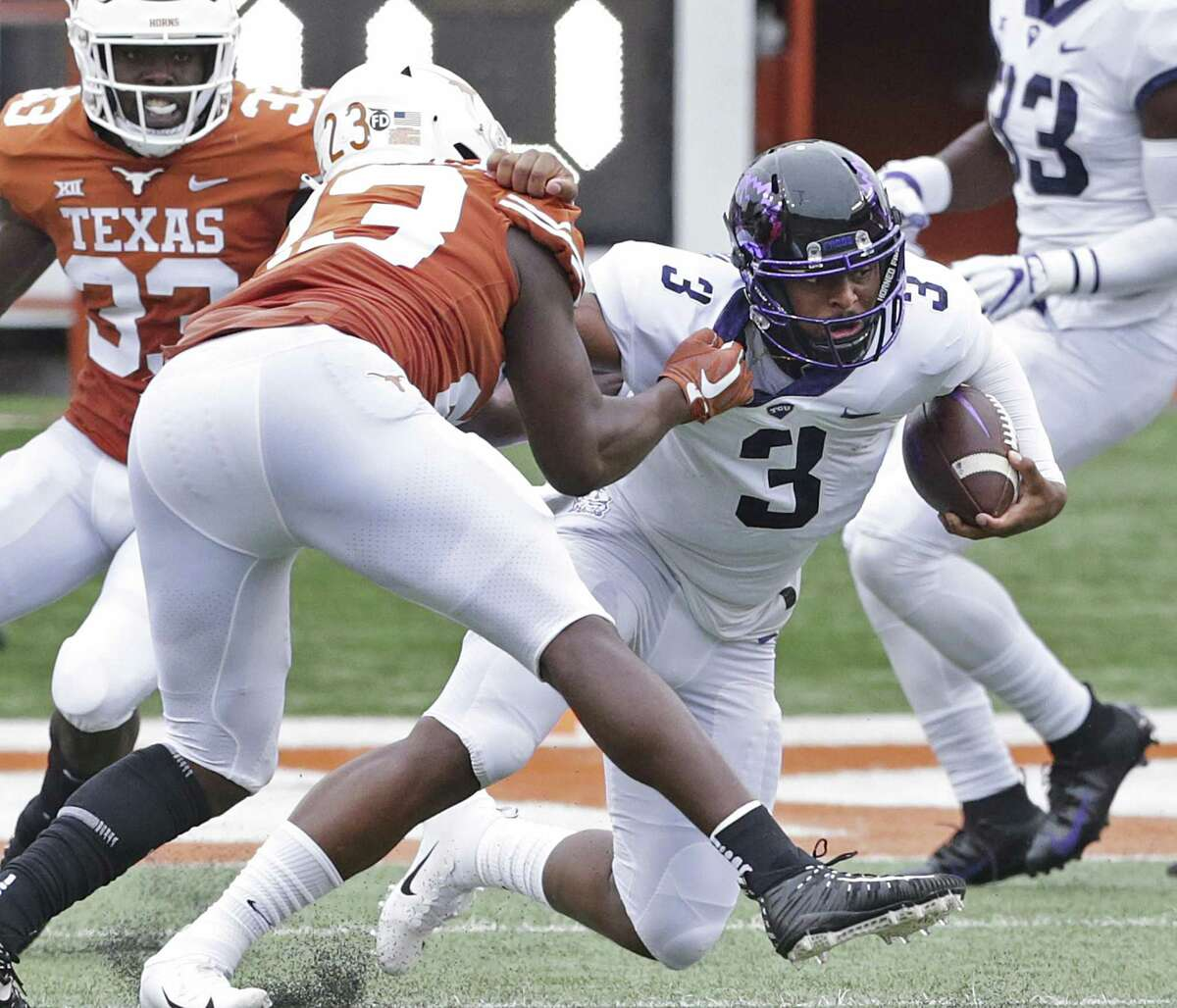 Frog quarterback Shawn Robinson is slung down by Jeffrey McCulloch to stop a scoring threat as UT hosts TCU at DKR Stadium on September 22, 2018.
