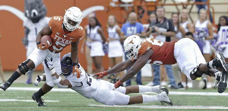 Longhorn running back Tre Watson gets some help from Calvin Anderson as he tries to get away from the Frog's Vernon Sott in the first half as UT hosts TCU at DKR Stadium on September 22, 2018.