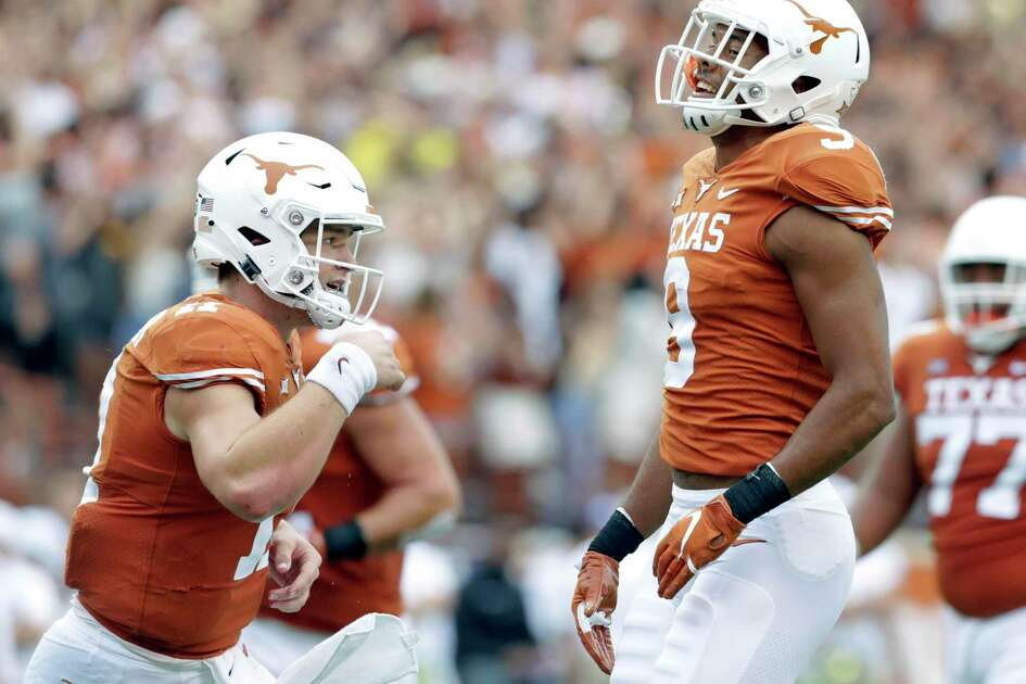 Colin Johnson (right) and Sam Ehlinger celebrate a touchdown pass in the second half which put the Longhorns on top as UT hosts TCU at DKR Stadium on September 22, 2018.