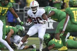 Stanford's Bryce Love, center, runs up the middle against Oregon during the first quarter of an NCAA college football game Saturday, Sept. 22, 2018, in Eugene, Ore. (AP photo/Chris Pietsch)