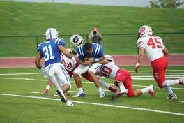 Clear Springs quarterback Garrett Rooker (12) is hit hard by Katy's Joseph Johnson (19) and Josh Garcia (40) Saturday at Challenger Columbia Stadium.