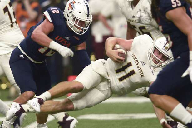 UTSA safety Andrew Martel (12) puts a hard hit on Texas State quarterback Tyler Vitt during college football action in the Alamodome on Saturday, Sept. 22, 2018.