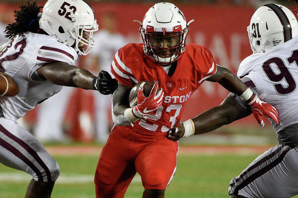 Houston running back Chandler Smith, center, runs past Texas Southern defensive lineman Darius Stapleton (52) defensive lineman Mark Wheeler (91) during the second half of an NCAA college football game, Saturday, Sept. 22, 2018, in Houston.