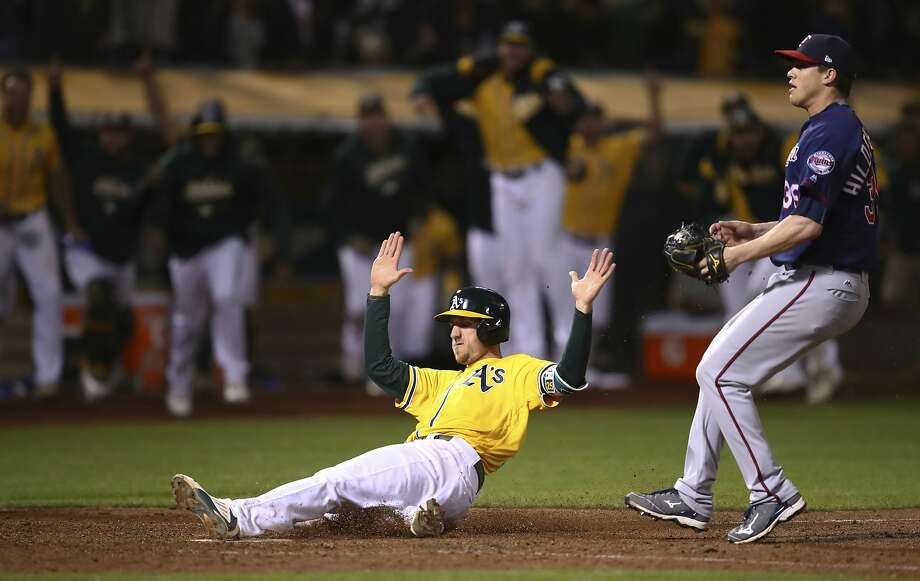 Stephen Piscotty slides home with the winning run in front of Twins reliever Trevor Hildenberger, who uncorked a wild pitch with two outs in the bottom of the ninth inning. Photo: Ben Margot / Associated Press