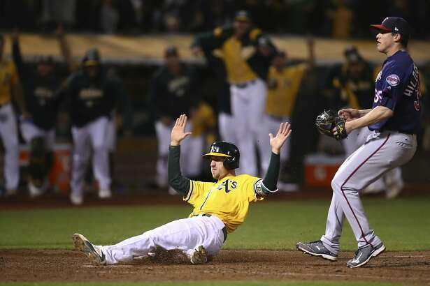 Oakland Athletics' Stephen Piscotty slides to score in front of Minnesota Twins' Trevor Hildenberger in the ninth inning of a baseball game Saturday, Sept. 22, 2018, in Oakland, Calif. Piscotty scored on a walk-off wild pitch by Hildenberger. (AP Photo/Ben Margot)
