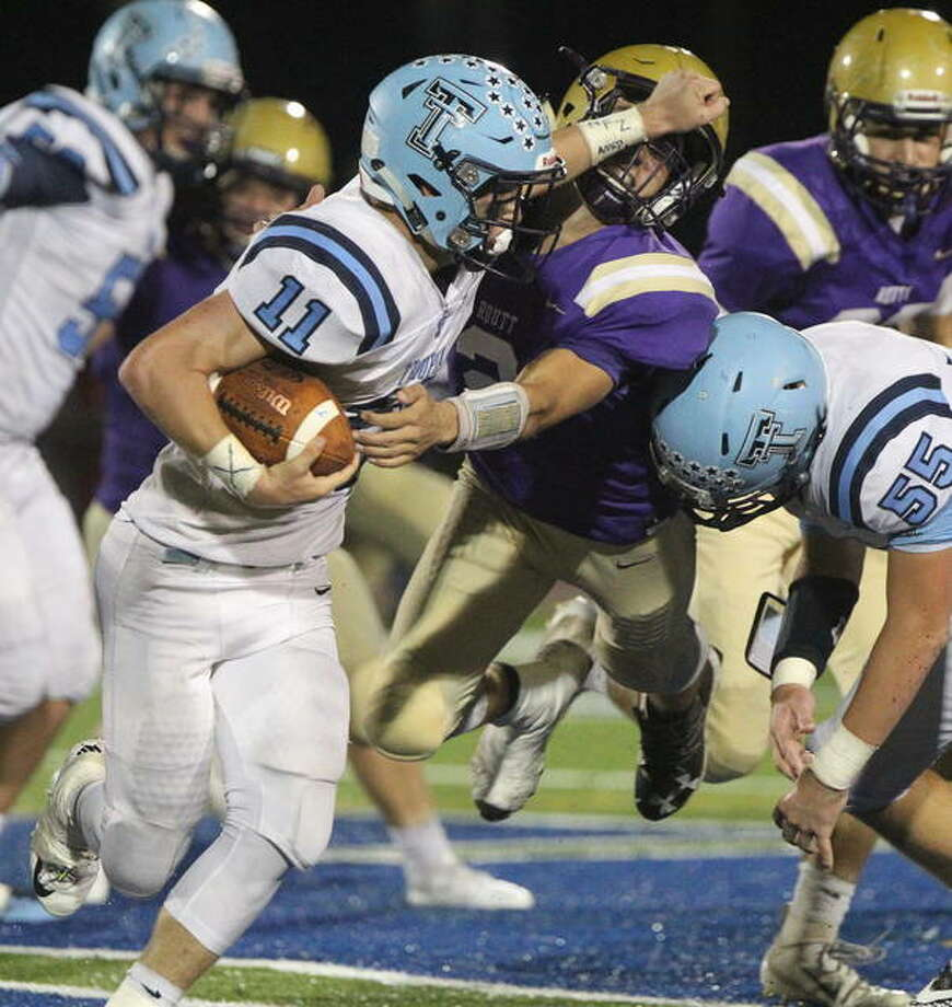 Triopia's Zach Thompson stiff-arms a lunging Routt tackler during a game at Illinois College Thursday night. Photo: Dennis Mathes | Journal-Courier