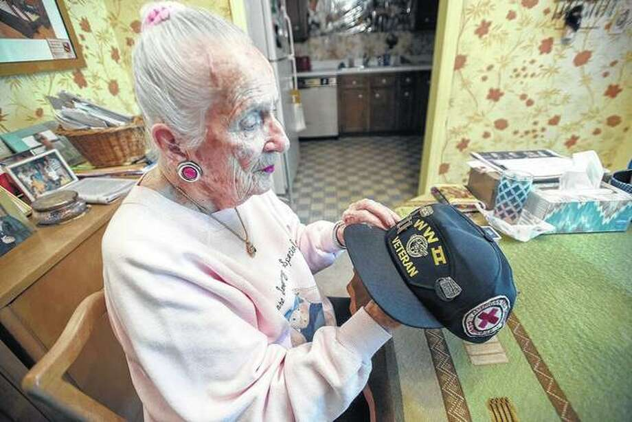 Jill Knappenberger, who served with the American Red Cross during World War II, looks at the pins and patches on her hat. Photo: Stephen Haas | News-Gazette (AP)