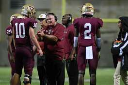 Cy Woods Head Coach Trent Faith, center, pumps up senior quarterback Carson Danner (10) during a second quarter timeout in the Wildcat's District 17-6A matchup with Langham Creek at Cy-Fair FCU Stadium on Sept. 20, 2018.