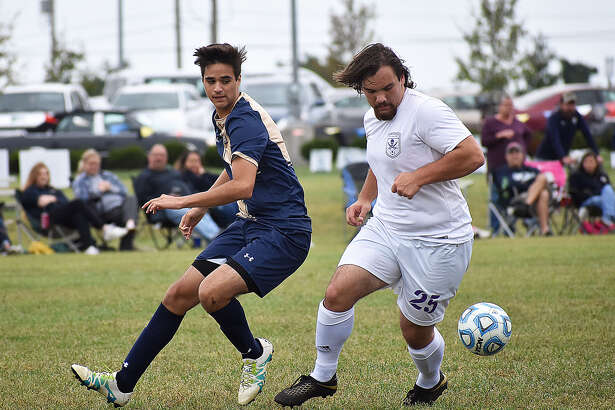 Father McGivney's Brandon Munoz, left, goes for a ball against a Valmeyer player during the first half.