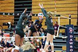 Dawson's Kynnedi Johnson (14) hits a shot between George Ranch's Kennedy Prince (5) and Allie Sczech (14) in a recent District 23-6A volleyball match.