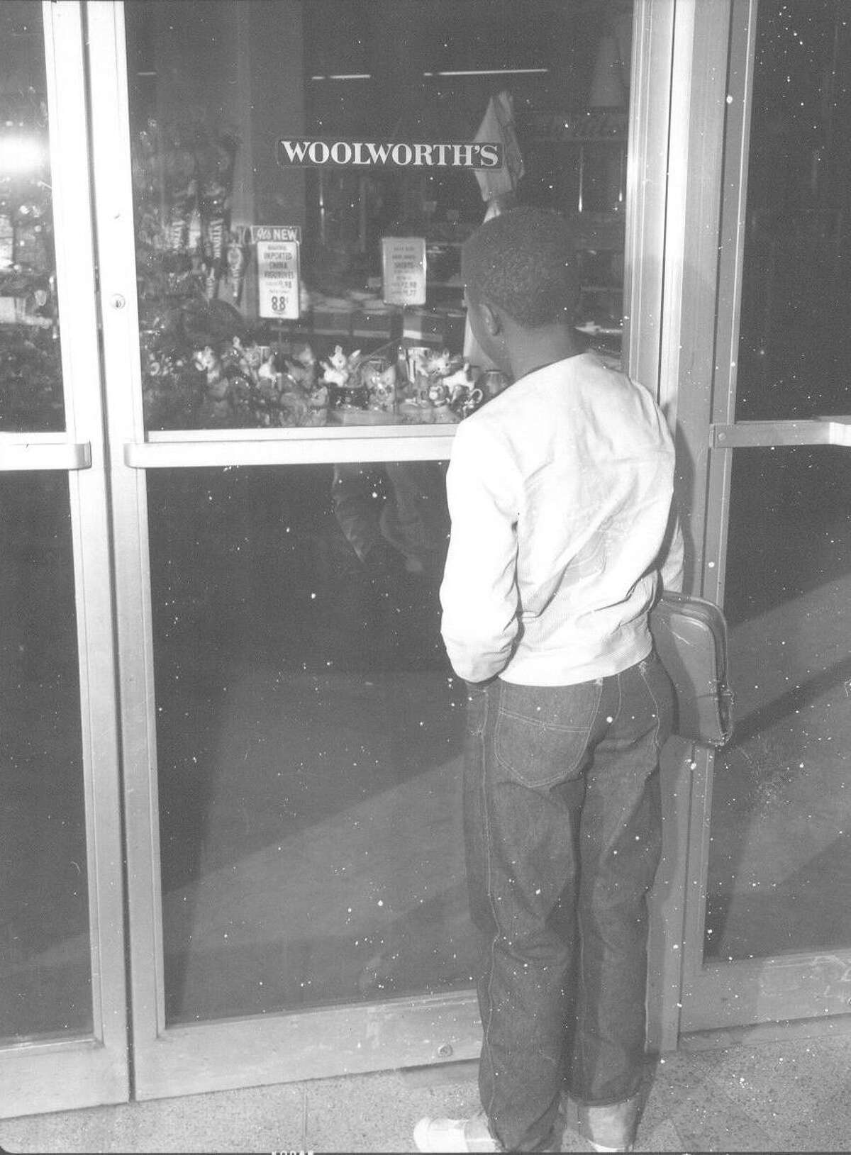 An African-American man waits outside the F.W. Woolworth Building in Alamo Plaza on March 16, 1960, when the lunch counter there became one of the first to stop barring black customers.