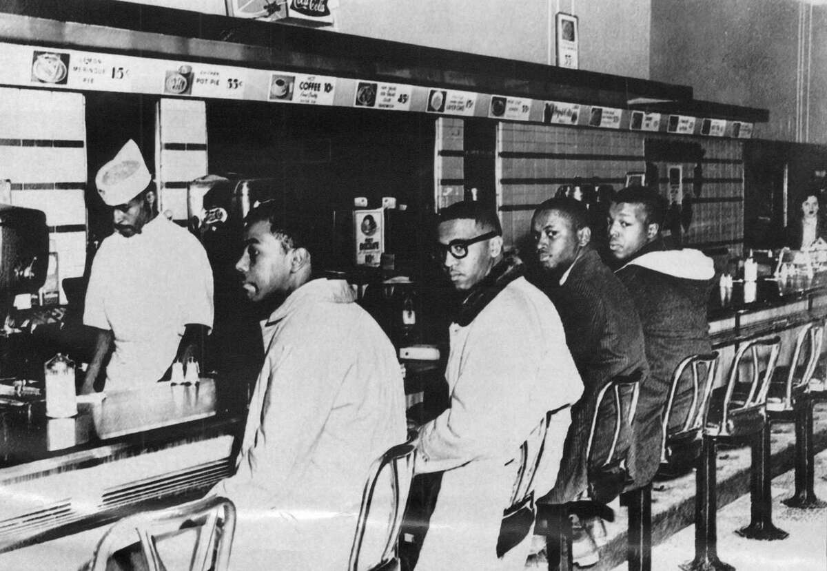 """Four college students, from left, Joseph McNeil, Franklin McLain, Billy Smith and Clarence Henderson, sit down at the all-white lunch counter of F.W. Woolworth Co. on Feb. 1, 1960, in Greensboro, North Carolina, where they were refused service. Their actions helped energize the American civil rights movement. The counter was displayed at the Smithsonian Institution - a reminder, one of the students said, to """"never let us forget from where we've come as a country."""""""