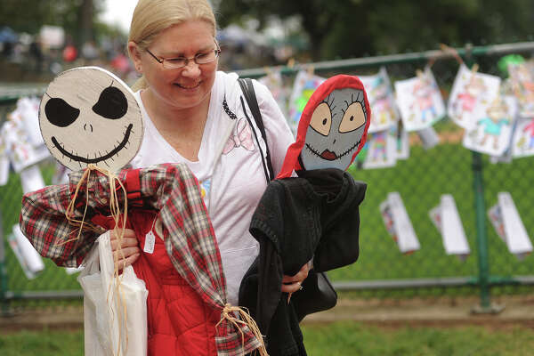 Donna Slater-Trefny, of Guilford, has her arms full of creepy characters as she shops at the 53rd Annual Pumpkin Festival at French Memorial Park in Seymour, Conn. on Sunday, September 23, 2018.