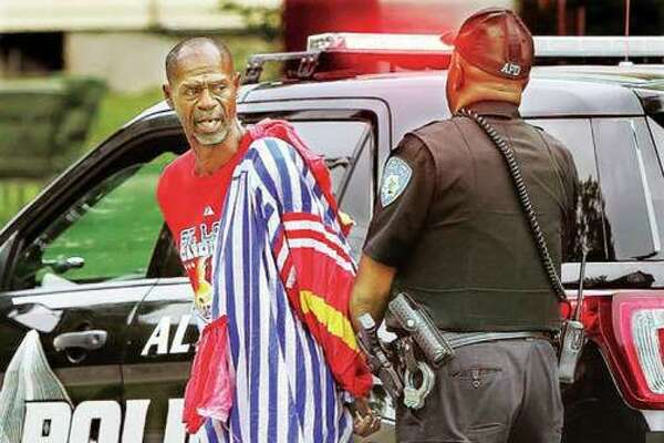 Ron Singleton, dressed in a clown suit he apparently, allegedly, burgled from an abandoned home, is arrested by an Alton police officer after an incident earlier this month.