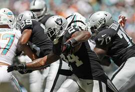 Oakland Raiders running back Marshawn Lynch (24) runs for yardage during the first half of an NFL football game against the Miami Dolphins, Sunday, Sept. 23, 2018, in Miami Gardens, Fla. (AP Photo/Brynn Anderson)
