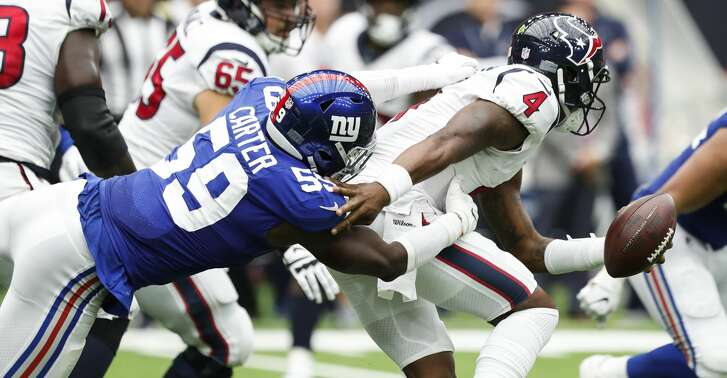 Houston Texans quarterback Deshaun Watson (4) is tackled by New York Giants linebacker Lorenzo Carter (59) after he was forced out of the pocket during the second quarter of an NFL football game at NRG Stadium on Sunday, Sept. 23, 2018, in Houston.