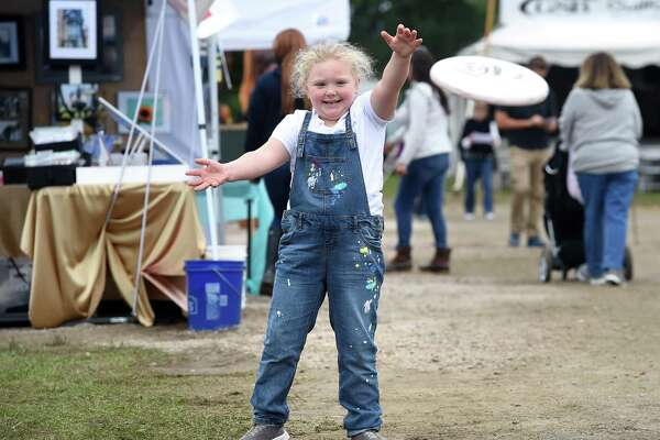 Makenna Munson, 6, of Bethel reaches for a frisbee thrown by a robotic frisbee thrower at the 160th annual Guilford Fair on September 23, 2018. The robotic frisbee thrower was built in 2013 for international competition by the Guilford robotics team, Apple Pi.