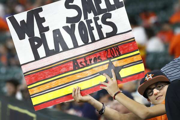 "A Houston Astros fan holds up a ""We Smell Playoffs"" sign before the start of an MLB baseball game at Minute Maid Park, Sunday, September 23, 2018, in Houston."