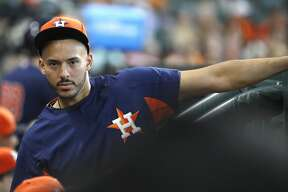 Houston Astros Carlos Correa keeps an eye out in the dugout during the first inning of an MLB baseball game at Minute Maid Park, Sunday, September 23, 2018, in Houston.