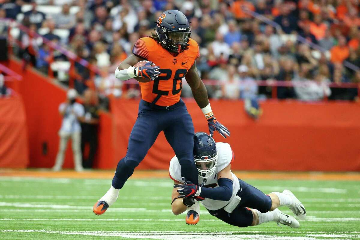 Syracuse's Jarveon Howard runs with the ball as UConn's Eddie Hahn attempts to make the tackle on Saturday.