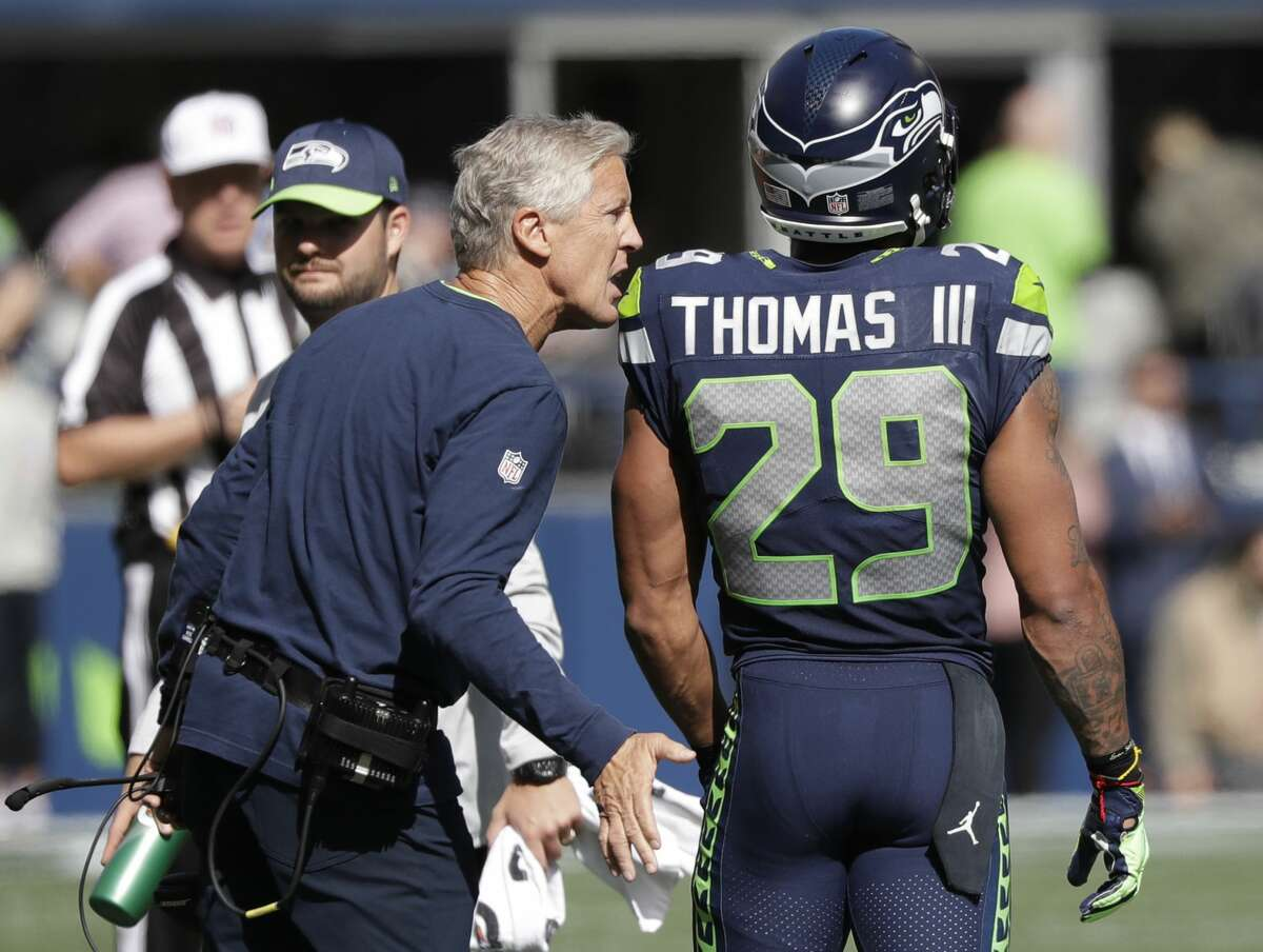 Seattle Seahawks head coach Pete Carroll, left, talks with free safety Earl Thomas during the first half of an NFL football game against the Dallas Cowboys, Sunday, Sept. 23, 2018, in Seattle. (AP Photo/Elaine Thompson)