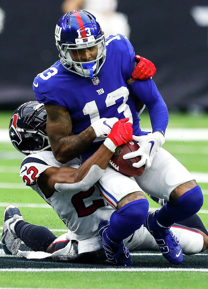 Houston Texans defensive back Aaron Colvin (22) tackles New York Giants wide receiver Odell Beckham (13) during the second quarter of an NFL football game at NRG Stadium on Sunday, Sept. 23, 2018, in Houston.