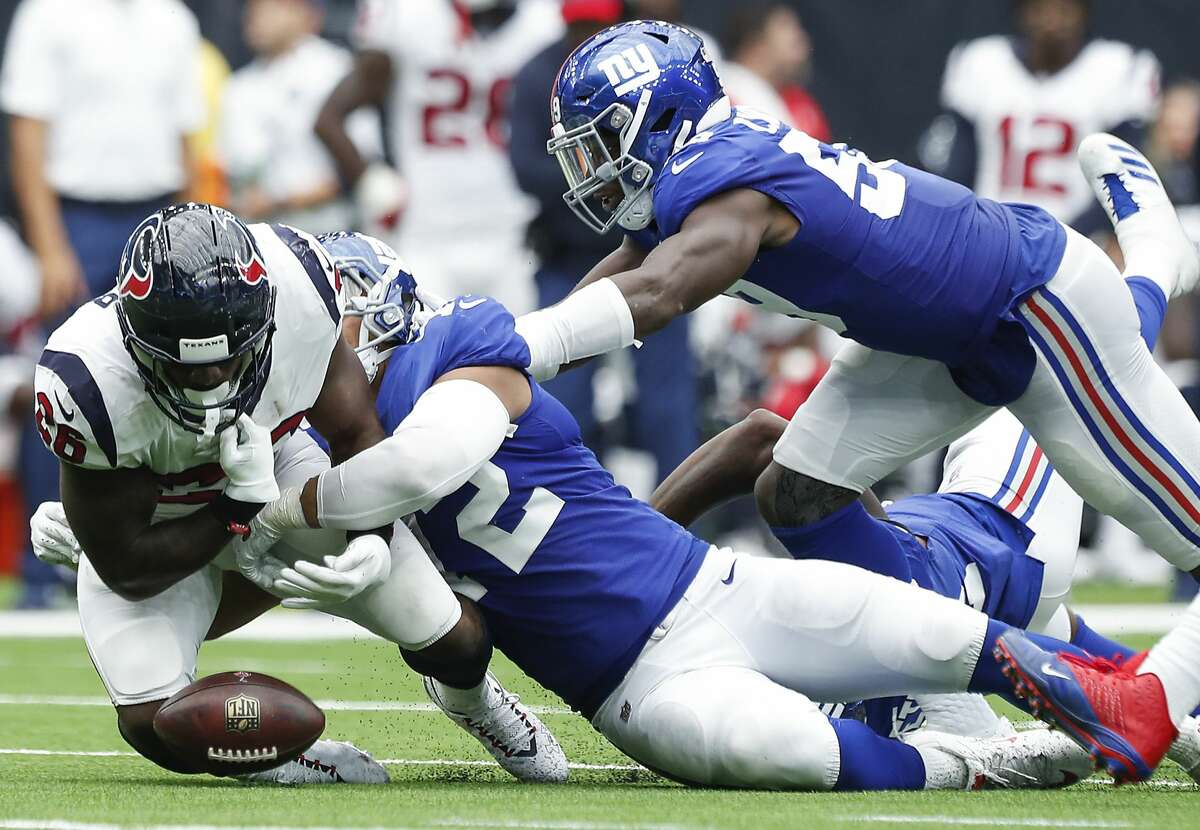 Houston Texans running back Lamar Miller (26) fumbles as he is tackled by New York Giants defensive end Kerry Wynn (72) during the third quarter of an NFL football game at NRG Stadium on Sunday, Sept. 23, 2018, in Houston.