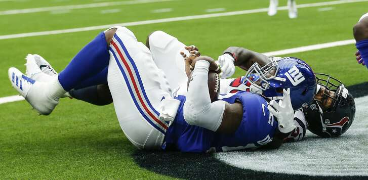 New York Giants linebacker Alec Ogletree (52) falls to the turf as he intercepts a pass in the end zone intended for Houston Texans running back Lamar Miller (26) during the fourth quarter of an NFL football game at NRG Stadium on Sunday, Sept. 23, 2018, in Houston.