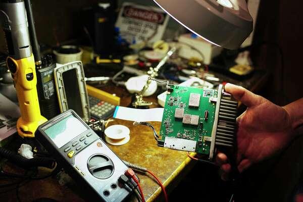 Chris deWaal, senior product engineer, displays a marine radio prototype he has been testing at Cedar Electronics in Chicago.