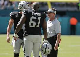 Oakland Raiders head coach Jon Gruden talks with center Rodney Hudson (61) and quarterback Derek Carr, left rear, during the second half of an NFL football game against the Miami Dolphins, Sunday, Sept. 23, 2018 in Miami Gardens, Fla. (AP Photo/Lynne Sladky)
