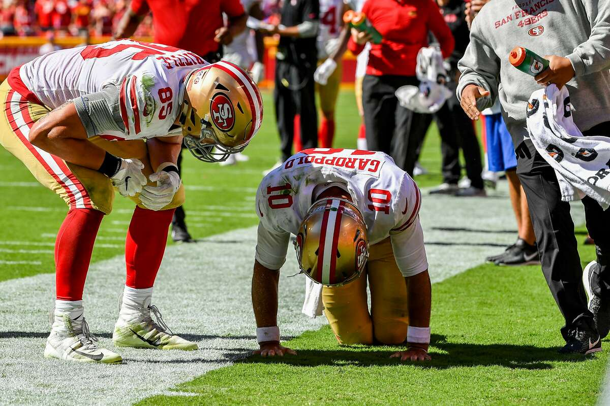 KANSAS CITY, MO - SEPTEMBER 23: George Kittle #85 of the San Francisco 49ers checks on injured teammate Jimmy Garoppolo #10 after a play in the fourth quarter of the game against the Kansas City Chiefs at Arrowhead Stadium on September 23rd, 2018 in Kansas City, Missouri. (Photo by Peter Aiken/Getty Images)