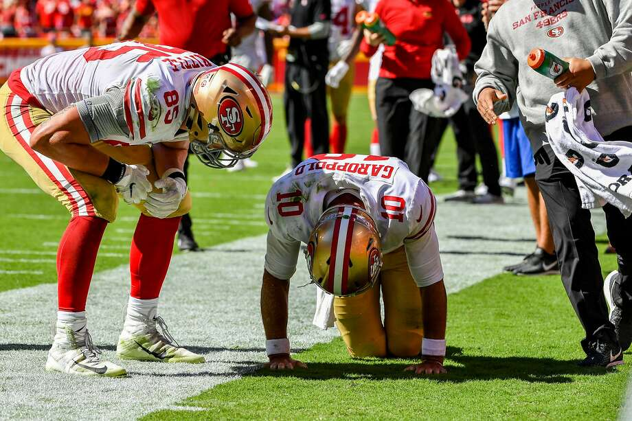 George Kittle #85 of the San Francisco 49ers checks on injured teammate Jimmy Garoppolo #10 after a play in the fourth quarter of the game against the Kansas City Chiefs at Arrowhead Stadium on September 23rd, 2018 in Kansas City, Missouri. Photo: Peter Aiken / Getty Images