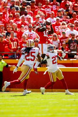 KANSAS CITY, MO - SEPTEMBER 23: Tyreek Hill #10 of the Kansas City Chiefs leaps in the air to make a catch against Adrian Colbert #27 and Richard Sherman #25 of the San Francisco 49ers during the second quarter fo the game at Arrowhead Stadium on September 23rd, 2018 in Kansas City, Missouri. (Photo by David Eulitt/Getty Images)