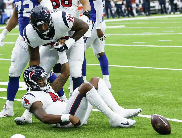 Houston Texans offensive tackle Julie'n Davenport (70) picks up quarterback Deshaun Watson off the turf after he was sacked during the second quarter of an NFL football game against the New York Giants at NRG Stadium on Sunday, Sept. 23, 2018, in Houston.
