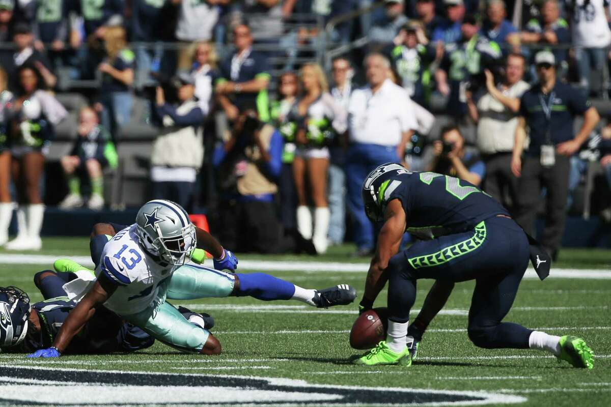 Seahawks safety Earl Thomas, right, recovers a pass intended for Cowboys wide receiver Michael Gallup (13) in the first quarter of Seattle's game against Dallas, Sunday, Sept. 23, 2018.
