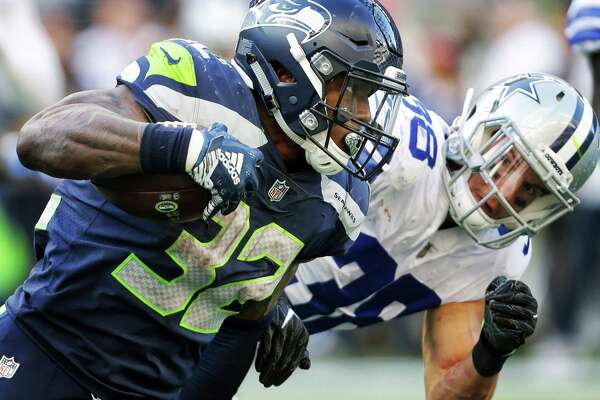 Seahawks running back Chris Carson (32) runs the ball past Cowboys safety Jeff Heath (38) in the fourth quarter of Seattle's game against Dallas, Sunday, Sept. 23, 2018.