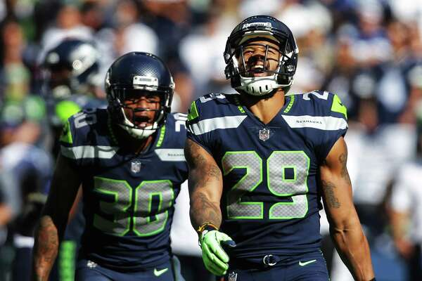Seahawks safety Earl Thomas and safety Bradley McDougald celebrate a tackle by Thomas in the first half of Seattle's game against Dallas, Sunday, Sept. 23, 2018.