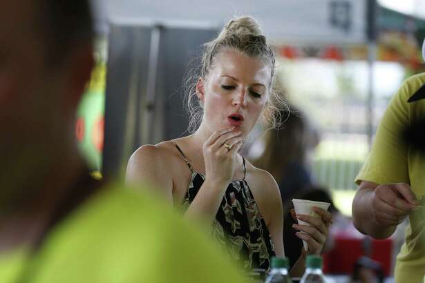 Monica Weis reacts to taste of Flavor and Fire's Black Mamba Six Get Bitten sauce during the 2018 Texas Hot Sauce Festival Sunday, Sept. 23, 2018, in Houston. The two day event was held at the Bayou City Event Center featured hundreds of hot and spicy products from around the country.