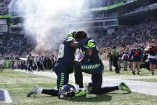 Twin brothers and Seahawks players Shaquill and Shaquem Griffin pray together before the start of Seattle's game against Dallas, Sunday, Sept. 23, 2018.