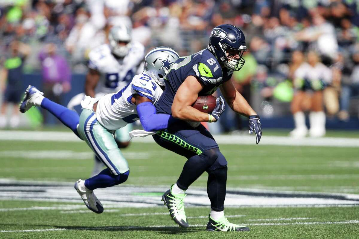 Seahawks tight end Nick Vannett is slowed by Cowboys corner back Chidobe Awuzie in the first half of Seattle's game against Dallas, Sunday, Sept. 23, 2018.
