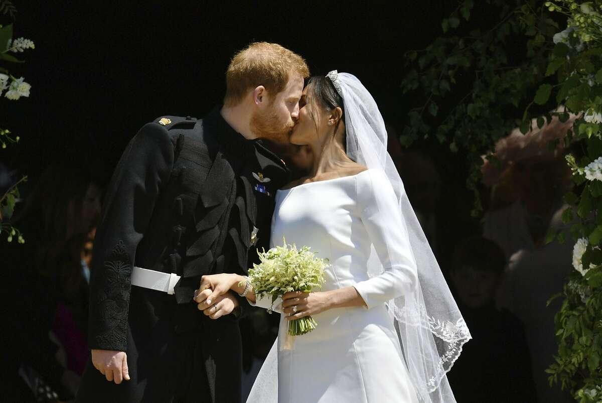 FILE - In this file photo dated Saturday, May 19, 2018, Britain's Prince Harry and Meghan Markle leave after their wedding ceremony at St. George's Chapel in Windsor Castle, in Windsor, England. Meghan Markle has revealed in a television documentary aired Sunday Sept. 23, 2018, that she had a piece of blue fabric from the dress she wore on her first date with Harry sewn into her wedding outfit. (Ben Birchhall/pool via AP, FILE)